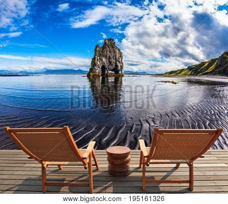 Concept of extreme northern tourism. Magic Rock Hvitsercur on northern coast of Iceland. Two wooden deck chairs are on the beach