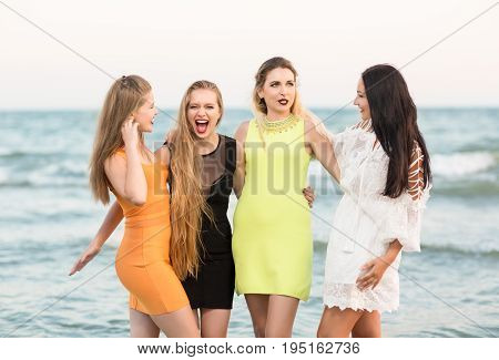 Attractive, good-looking and funny girls with pretty long hair and in multi-colored, fashionable and modern dresses, look happy on the sea beach background. Beautiful ladies on the beach.