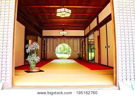 A round door in a Japanese temple leading to a garden.