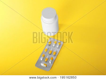 Close-up various colorful prescripted drugs. Antibiotics, painkillers as medical treatment. A small white bottle for vitamins, pills, painkillers and tablets.