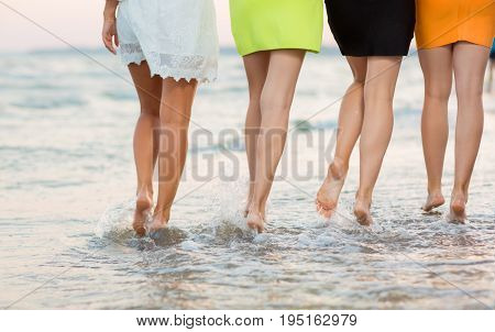 Adorable long-legged girls walk near the sea on the sand. Long and smooth female legs on the background of the sea, view from back. Close-up of a cute sports women's legs. Beautiful girls on a tropical beach sea.
