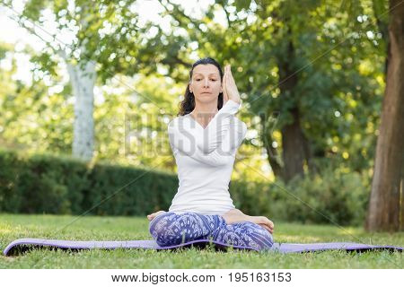 Peaceful girl meditating in a morning sunny park. Concentrated thoughtful lady in a lotus position stretching her hands. Brunette female doing different exercises.