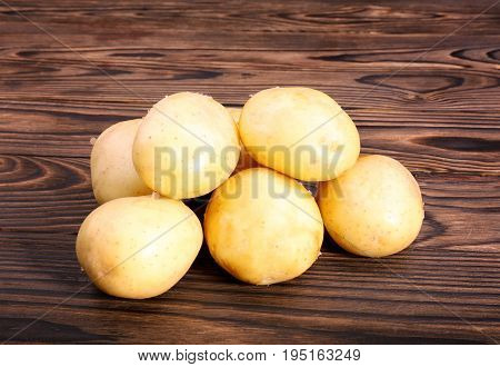 Some raw new potatoes on a dark brown wooden table. A large pile of fresh and young potatoes. Organic new light brown potatoes. Fresh vegetables. Summer harvest tasty and new potatoes.