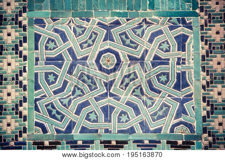 Close up shot of some Arabic decorations on a wall.