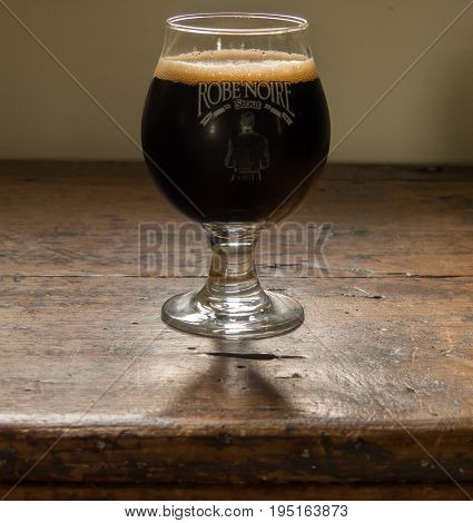 Photo taken on an old wooden chest this cup is filled with stout beer.