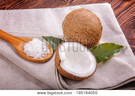 Close-up coconuts on a gray piece of cloth on a dark wooden background. Bright cut coco and green leafs. Delicious coconuts on a brown table. Spoon filled with white coconut flakes.