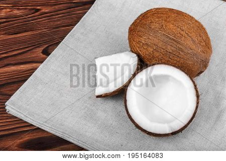 Close-up tasteful coconuts on a dark wooden background. Healthful coconut on a bright gray piece of cloth. Delicious natural ingredients. Exotic tropical nuts.