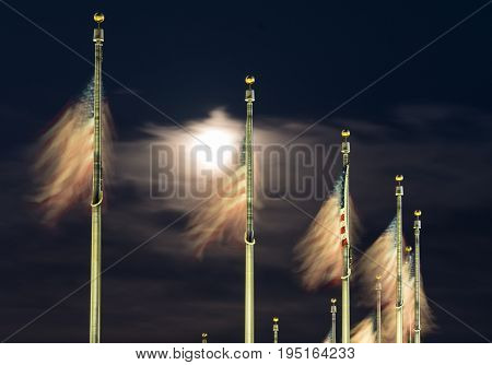 US Flags flutter in front of moon by Washington Monument on a clear night in Washington DC, United States of America