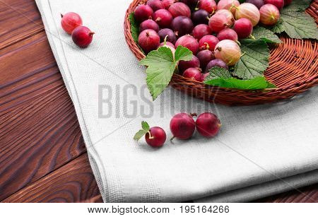A brown wooden basket with multi-colored gooseberries on white fabric on a dark brown background. Colorful red berries full of nutritious vitamins. Close-up ripe fresh red berries. Delicious berries.
