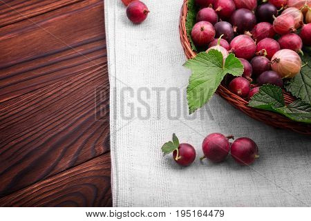 Close-up picture of delicious, ripe and bright red gooseberries in a horizontal position on a dark brown wooden table. Gooseberries different shades of bright red color.