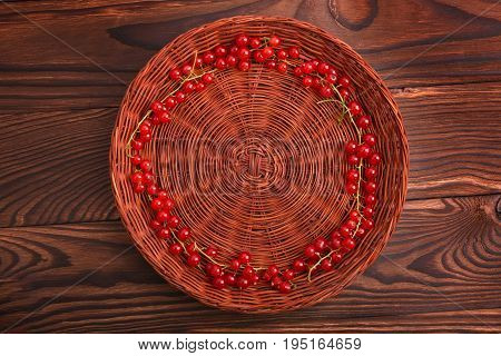 A colorful composition of a brown basket with juicy red currant on a dark wooden table. Fresh,mature, healthy and ripe red currant are lying inside, forming a good circle.