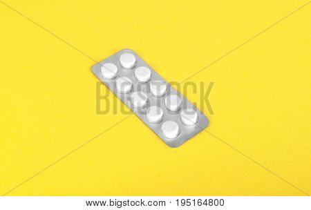 Close-up of pills, medicinal vitamins, tablets and drugs.      Packaging for drugs: antibiotics, painkillers, vitamins and aspirin tablets. White pill and capsules on a bright yellow background