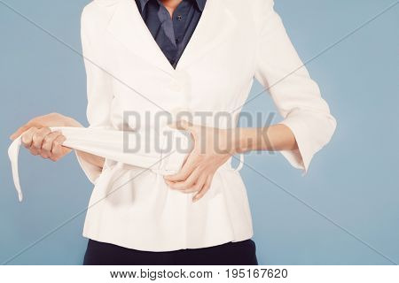 Midsection of a businesswoman adjusting belt against blue background