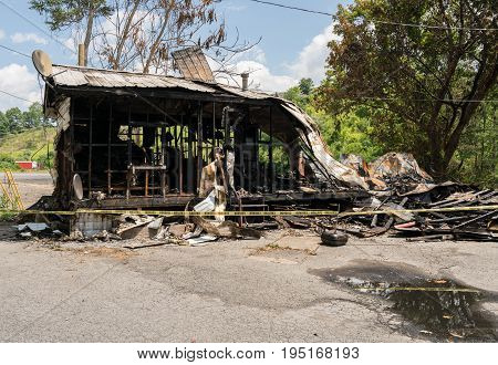 Burnt or burned out ruins of wooden framed home with metal roof
