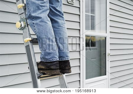 Man standing on ladder with house exterior background