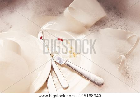 Closeup of a stack of dirty dishes and silverware in sink with bubbles