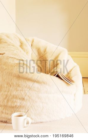 Closeup of a furry beanbag with book and coffee cup