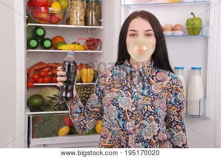 Young girl holding cola and making a big bubble with a chewing gum on the refrigerator background