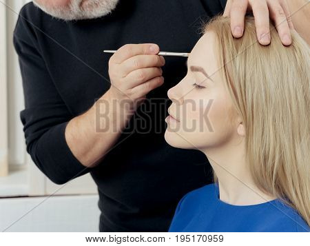 Woman getting makeup on face skin with powder brush in male hand. Adorable fashionable girl with long blond hair in beauty salon. Visage cosmetics make up. Beauty youth