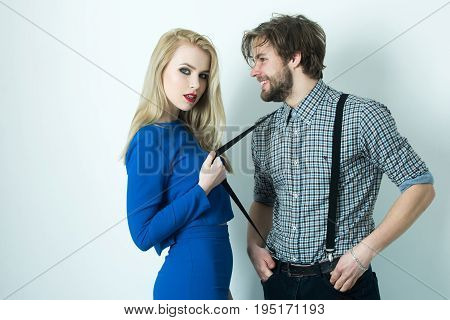 Girl and man posing on white background. Pretty woman or girlfriend in blue dress pulling suspenders of happy boyfriend or macho smiling. Fashionable couple in love. Fashion vogue
