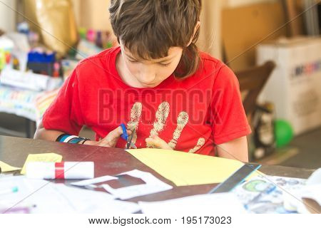 indoor portrait of young creative preteen boy making art and crafts at home