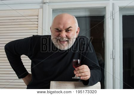 Man winking with glass of wine. Happy pensioner or senior person with grey beard in black sweater in room on window background. Alcohol and appetizer. Unhealthy lifestyle and bad habits poster