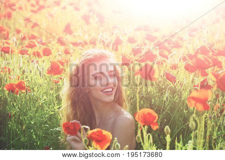 beautiful woman on poppy field with long hair bare shoulder and smiling face