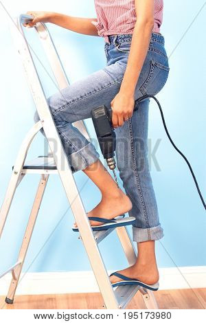 Woman Holding Power Drill on Stepladder