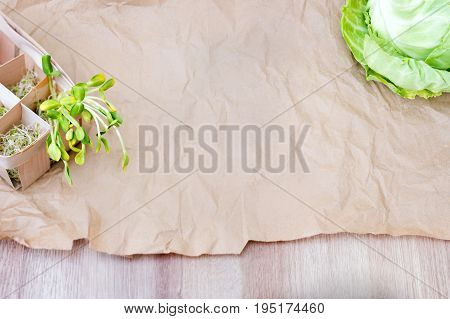 Mixed organic micro greens and cabbage on craft paper. Fresh sunflower and heap of alfalfa micro green sprouts for healthy vegan food cooking. Healthy food and diet concept. Cut microgreens, top view with copy space