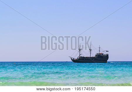 Black pirate ship sails along the coast