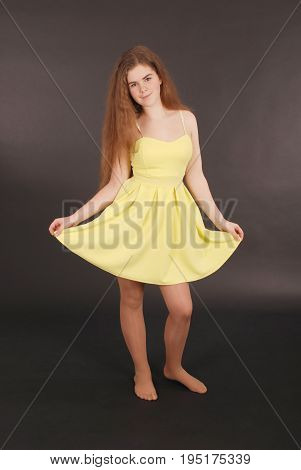 Young girl in yellow dress isolated on black background
