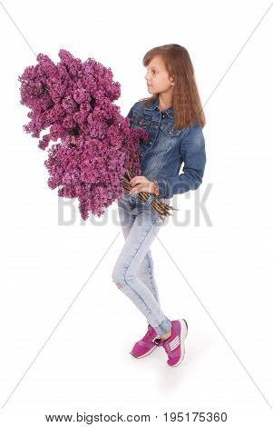 Teenage girl standing with lilac in both hands. Isolated on white background