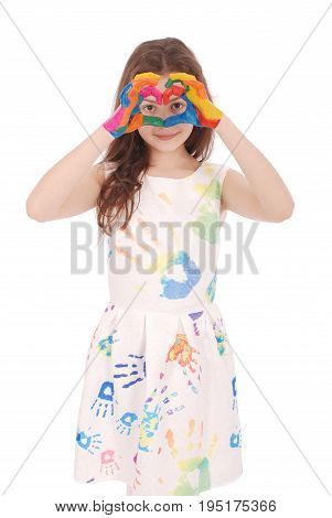 Adorable smiling little girl with the colored hands and dress shows the heart isolated on a white background