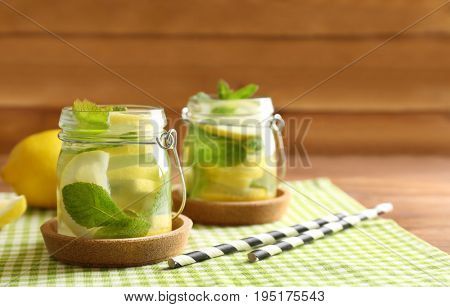 Jars of fresh lemonade on wooden background