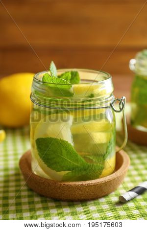 Jar of fresh lemonade on wooden background