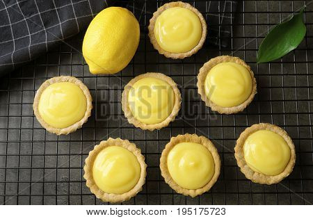 Tasty cookies with lemon curd on cooling rack