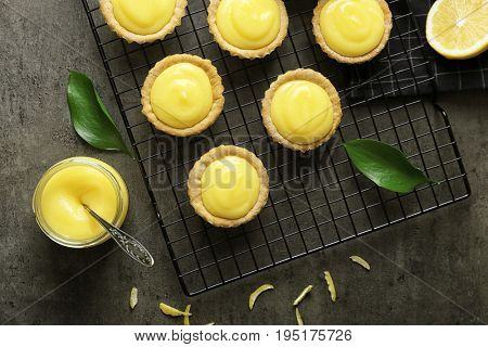 Composition with tasty cookies, lemon curd and cooling rack on table