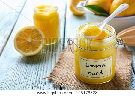 Glass jar with delicious lemon curd on wooden table
