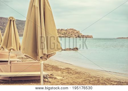 Deserted beach with sun umbrellas and sun beds on a cloudy summer day close-up. Greece island Crete. Photo toned