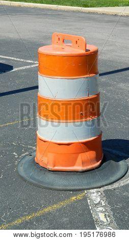 Single trafic barrel standing upright on asphalt surface.