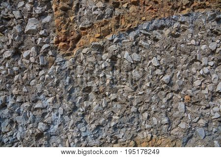 Grey pattern of gravel stone wall texture or background with orange(brown) and grey streaks