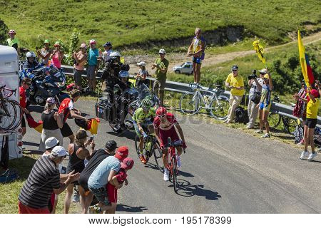 Col du Grand ColombierFrance - July 17 2016: The cyclists Majka and Zakarin riding through a crowd of spectators on the road to Col du Grand Colombier in Jura Mountains during the stage 15 of Tour de France 2016.