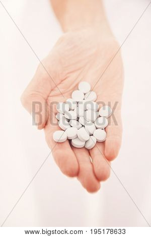 Closeup of a hand holding out many pills