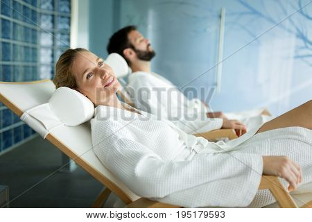 Handsome man and beautiful woman spending time and relaxing in spa wearing bathrobes