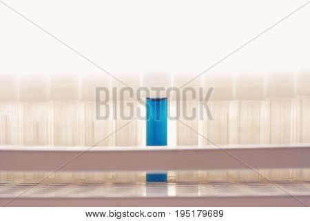 Blue test tube amongst empty test tubes
