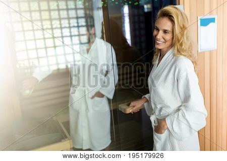 Attractive man and beautiful woman in sauna wearing bathrobes
