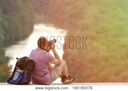 Man with a backpack taking photos with hill on the background of the forest and the river. Tonning