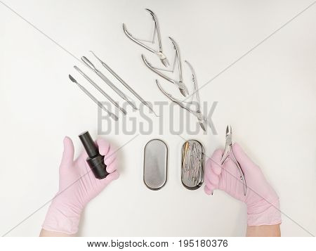 Two Female Hands In Gloves. Nail Polish And Tongs In Hands. Tools For Manicure. White Background, To