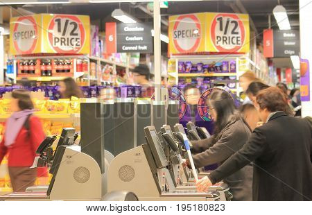 MELBOURNE AUSTRALIA - JUNE 30, 2017: Unidentified people use self check out cashers at Coles supermarket.