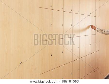 Businessman's hand opening locker in office